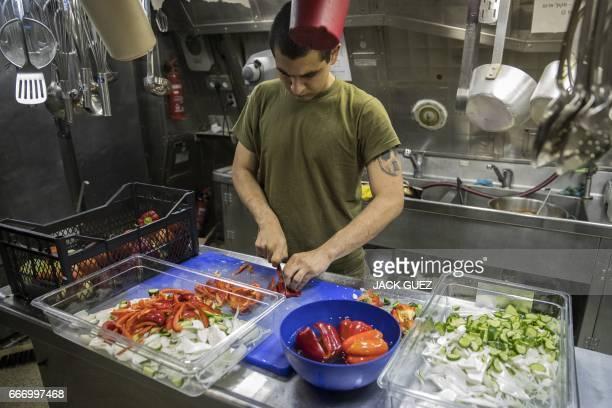 "Israeli soldier onboard the Israeli vessel Saar 5 Class Corvette ""INS Hanit"" prepares food during the ""Novel Dina 17"" exercise in the Mediterranean..."