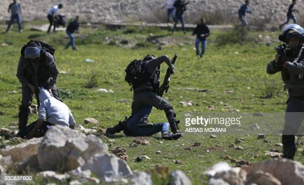 TOPSHOT Israeli soldier scuffle with Palestinian demosntartors on March 12 2018 in the West Bank town of Birzeit near Ramallah during a protest by...