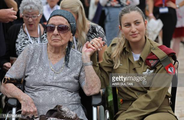 Israeli soldier Shira Tessler holds the hand of her grandmother Holocaust survivor Hanna Tessler during a ceremony marking the annual Holocaust...