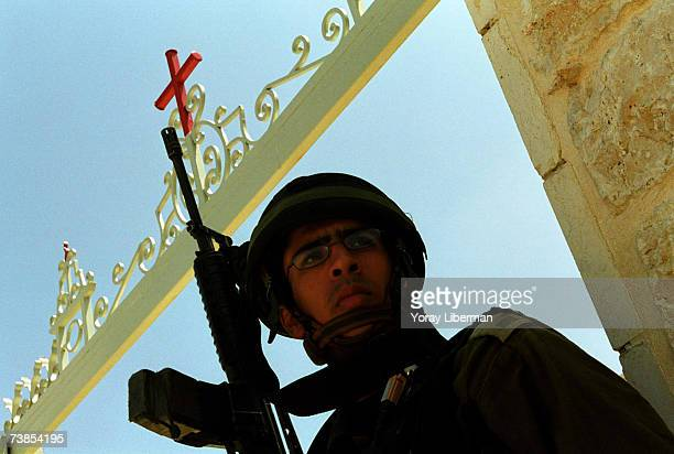 Israeli soldier stands next to a gate of a church with a red cross on it in the Palestinian city of Bethlehem on May 01 2002 in the West Bank...