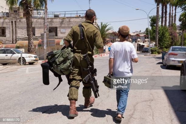Israeli soldier walks with Jewish settler on Shuhada street in the old town of Hebron which is under Israels military control on June 14 2018 Most of...