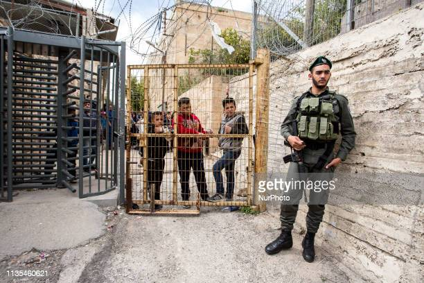 Israeli soldier watches the entrance to the Abraham mosque while Palestinian boys look at him from outside in Hebron West Bank on April 6 2019...