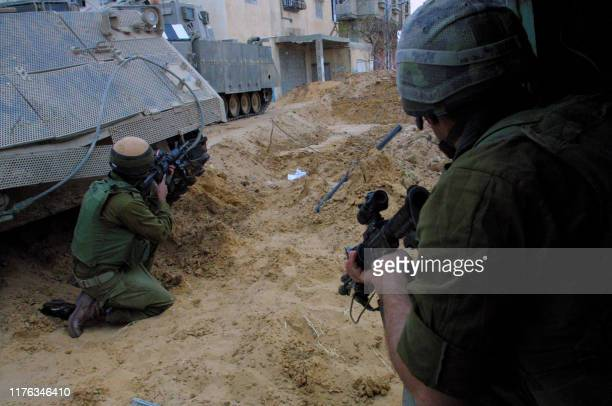 Israeli soldiers aim their guns during an exchange of fire with Palestinians following an army raid on the southern Gaza Strip town of Rafah, 15...
