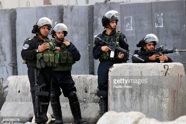 Israeli soldiers aim their M16s at Palestinian protesters at the Israeli military checkpoint Qalandia near the entrance of the Palestinian city of...
