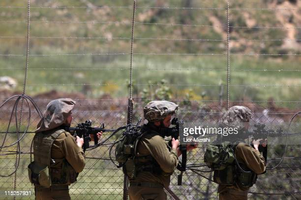 Israeli soldiers aim weapons along Syria's border with Israel as demonstrators try to cut through a line of barbed wire and head into the...