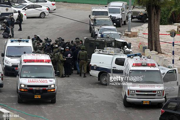 Israeli soldiers and borderguards gather at the site of a reported shooting attack that slightly wounded an Israeli female soldier near the Ibrahimi...