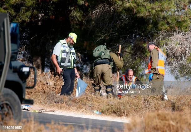 Israeli soldiers and forensic experts inspect the scene where the body of an Israeli soldier was found with multiple stabs near the settlement of...