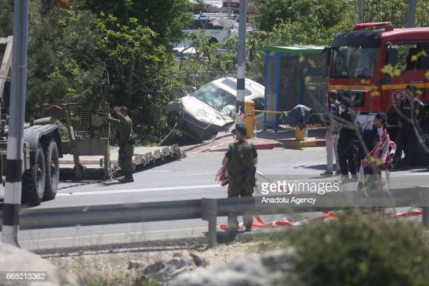 Israeli soldiers and police inspect the scene of a car ramming attack near the Israeli settlement of Ofra north of Ramallah 06 April 2017 One Israeli...