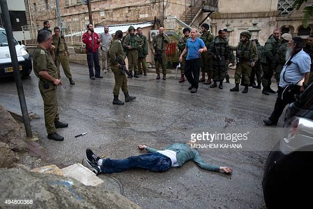 Israeli soldiers and settlers gather around the body of a Palestinian man who tried to stab a soldier at the Jewish settlement of Beit Hadassah in...