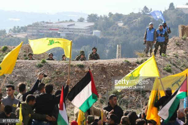 Israeli soldiers and UN peacekeepers look at Lebanese supporters of the Shiite Hezbollah movement attending a rally against the US president's...