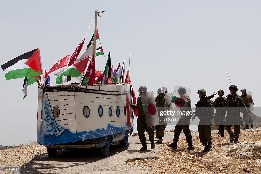 Israeli soldiers approach a replica of the Gaza aid flotilla used by Palestinians near an Israeli barrier, as they object to Israel's attack on the flotilla earlier this week, on June 4, 2010 in Bil'lan, the West Bank. Israel has faced international criticism over the deadly raid on May 31, aboard a ship carrying humanitarian aid to the Gaza Strip.