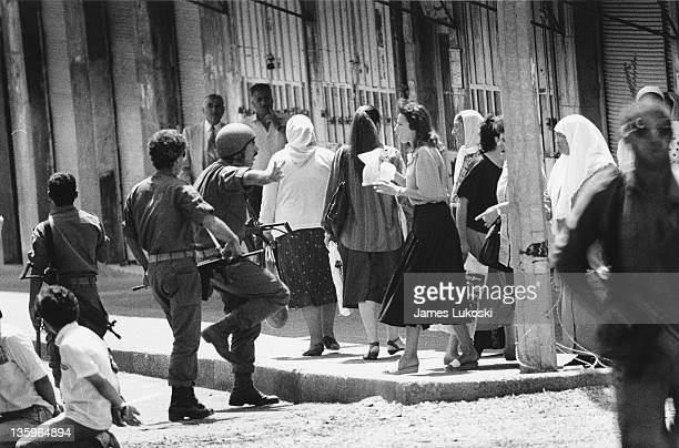 Israeli soldiers are confronted by a group of women in Ramallah West Bank during the IsraeliPalestinian conflict circa 1990 On the left are two...