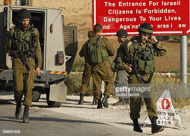 Israeli soldiers are seen at one of the entrances of the Palestinian village of Yatta in the occupied West Bank on June 92016 after the army entered...
