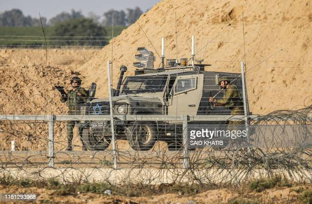 Israeli soldiers are seen next to a military vehicle across the barbed-wire border fence with the Gaza Strip during clashes following a Palestinian...