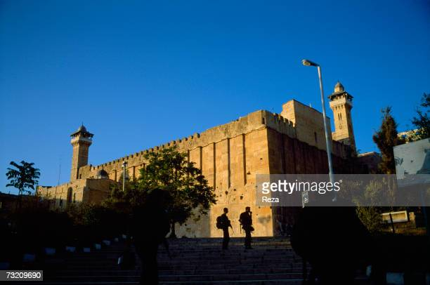 Israeli soldiers are silhouetted in front of the building called the Cave Of The Patriarchs on May 2001 Hebron West Bank The site is holy for both...