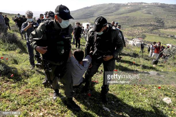 Israeli soldiers arrest a demonstrator as Palestinians and foreign activists gathered to plant trees in a field that is under the risk of being...