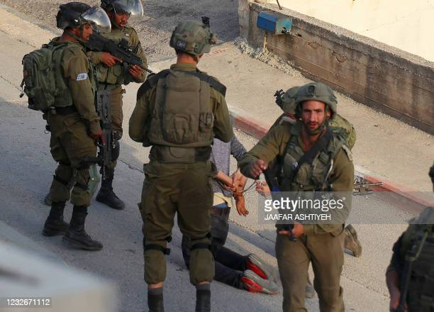Israeli soldiers arrest a man during a security operation in the Palestinian village of Aqraba, east of Nablus in the occupied-West Bank, on May 3,...