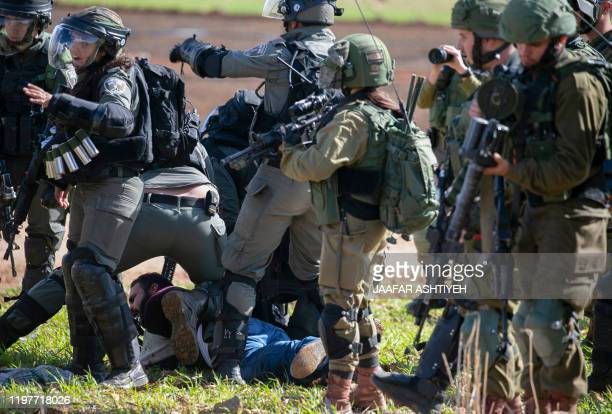Israeli soldiers arrest a Palestinian protester during a demonstration against a US brokered Middle East peace plan near the West Bank village of...