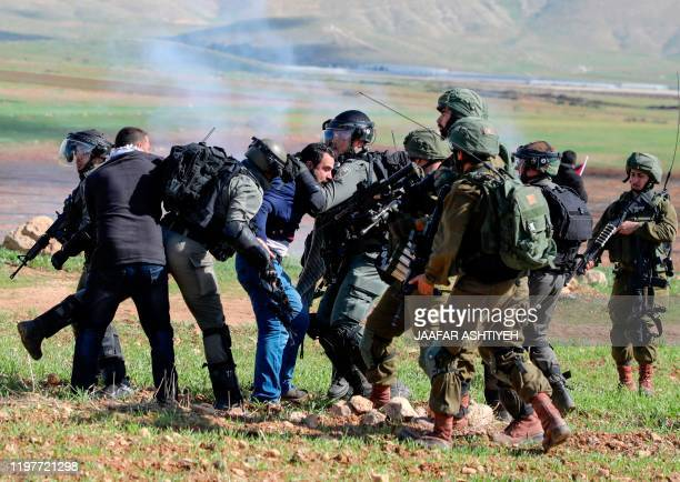 Israeli soldiers arrest a Palestinian protester during a demonstration against a US brokered Middle East peace plan outside the West Bank village of...