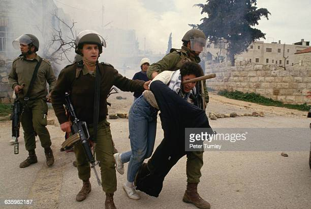 Israeli soldiers arrest a Palestinian young man in the West Bank