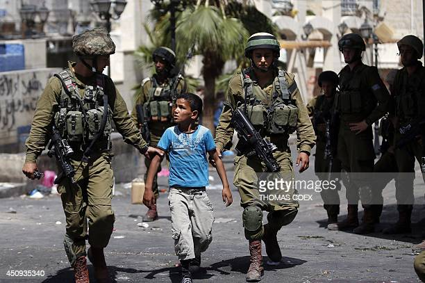 Israeli soldiers arrest a young Palestinian boy following clashes in the center of the West Bank town of Hebron, on June 20, 2014. Israeli soldiers...