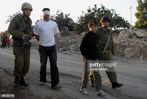 Israeli soldiers arrest two Palestinian youths following a stonethrowing incident during a demonstration marking the first anniversary of the death...