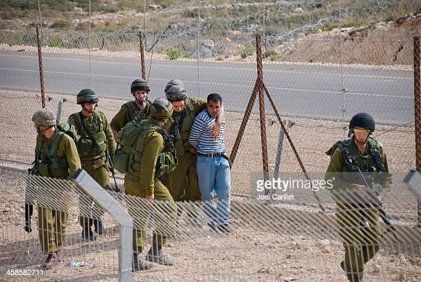 Israeli soldiers arresting a Palestinian man in Bil'in