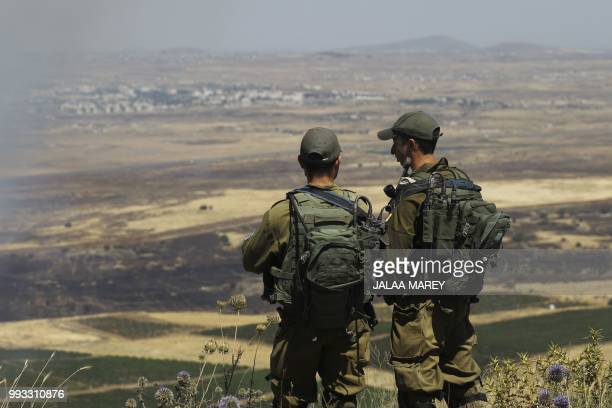 Israeli soldiers at an army base in the Israeliannexed Syrian Golan Heights look out across the southwestern Syrian province of Quneitra visible...