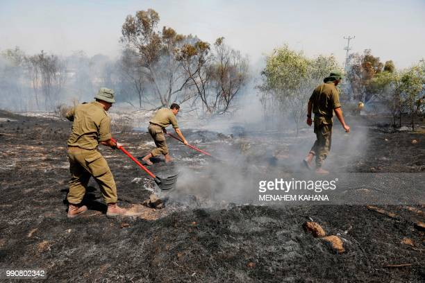 Israeli soldiers attempt to extinguish a fire in a forest field near the Kibbutz of Kissufim along the border with the Gaza Strip on July 3 2018...