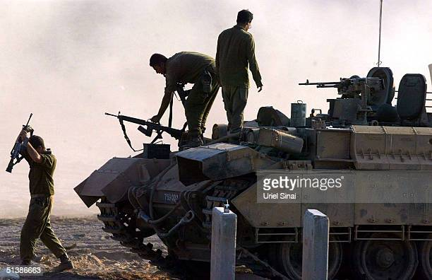 Israeli soldiers break for a rest on the Israeli side of the Green Line near the Gaza Strip town of Beit Hanun October 3 2004 in Gaza Strip Israeli...