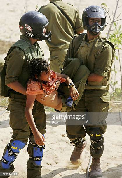 Israeli soldiers carry a Jewish settler youth in the Jewish settlement of Shirat Hayam on August 17 2005 in the southern Gaza Strip Thousands of...