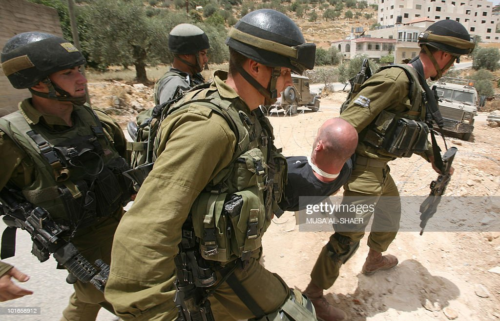 Israeli soldiers carry away a protester as Palestinian, Israeli and foreign peace activists protest against Israel's controversial separation barrier in the West Bank village of Beit Jala, near the biblical town of Bethlehem, on June 6, 2010.