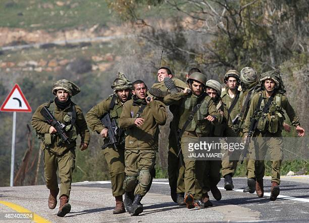 Israeli soldiers carry their injured comrade in the divided village of Ghajar after an antitank missile hit an army vehicle in an occupied area on...
