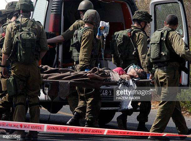 Israeli soldiers carry wounded Palestinian Raghad Khadour, one of two assailants who rammed a car into a bus stop used by Israelis in the occupied...