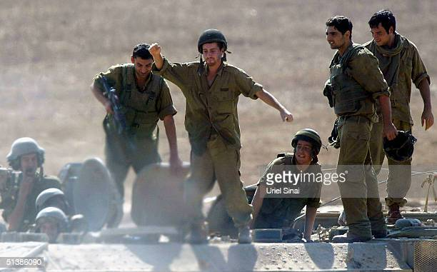 Israeli soldiers celebrate as they break for a rest on the Israeli side of the Green Line near the Gaza Strip town of Beit Hanun October 3 2004 in...