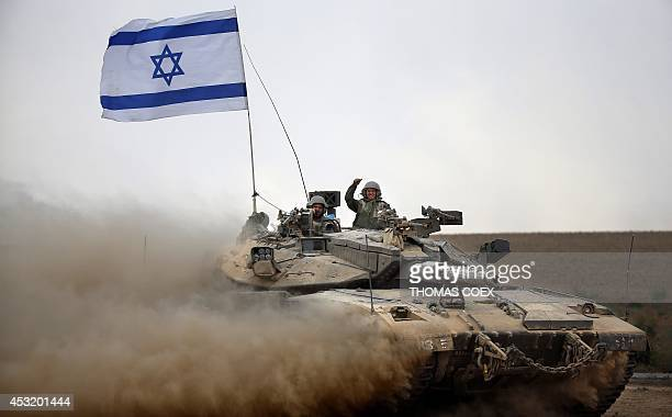 Israeli soldiers celebrate on board their Merkava tank near the border between Israel and the Gaza Strip as they return from the Hamascontrolled...