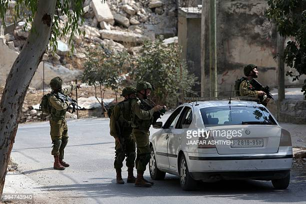Israeli soldiers check a car as they prevent Palestinians from leaving the northern West Bank village of Madama on August 24 2016 during searches...