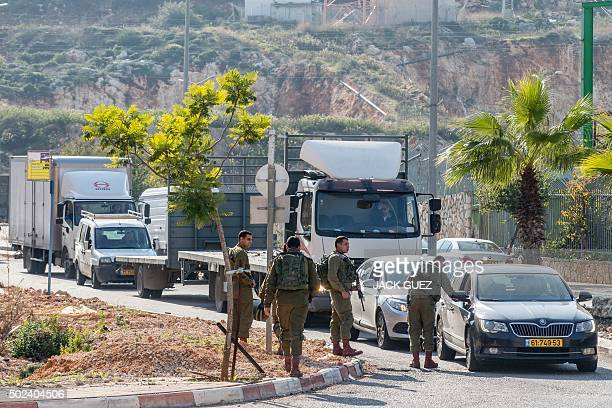 Israeli soldiers check vehicles near the scene where a Palestinian assailant was shot dead after he stabbed two Israeli security guards at an...