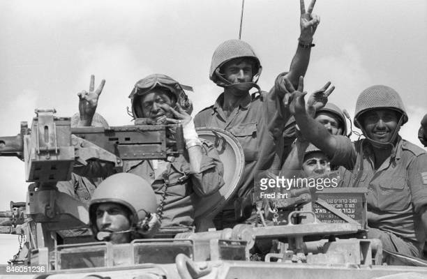 Israeli soldiers cheering and waving while driving by with their troops in tanks On the Golan Heights during the Yom Kippur war