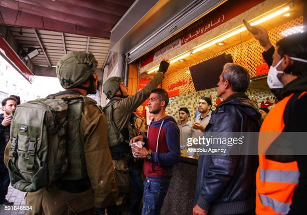 Israeli soldiers close stores of Palestinians during a protest against US President Donald Trumps announcement to recognize Jerusalem as the capital...
