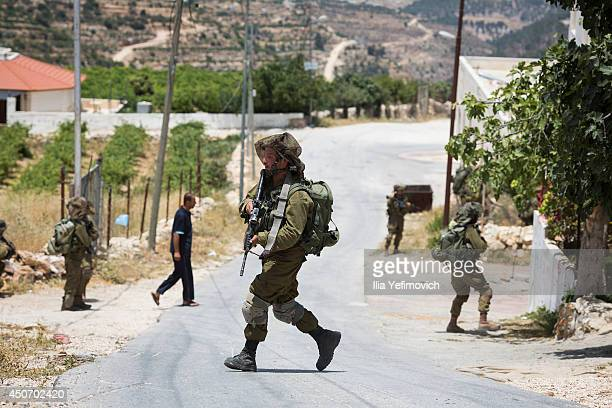 Israeli soldiers conduct a search mission during the fourth day into the search of three missing teenagers June 16 2014 in Halhul West Bank Israeli...