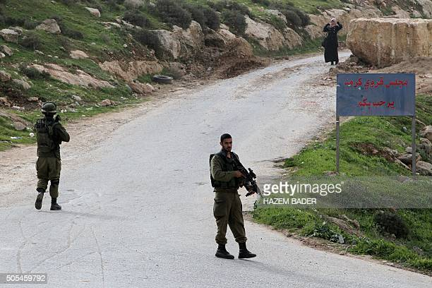 Israeli soldiers control an acess to the Palestinian village of Karma southwest of the flashpoint city of Hebron in the southern West Bank on January...