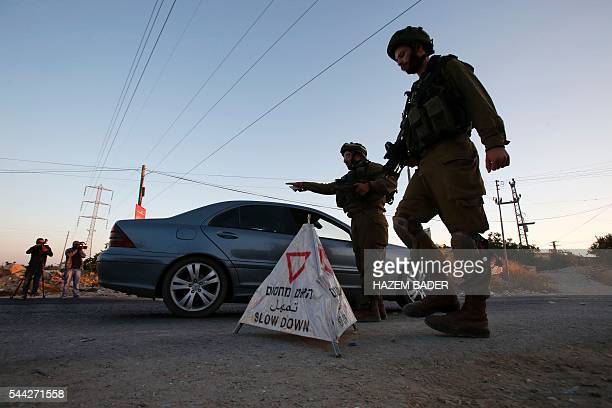 Israeli soldiers control check vehicles at a mobile checkpoint on the main exit road from the West Bank town of Hebron on July 3 as the army keeps...
