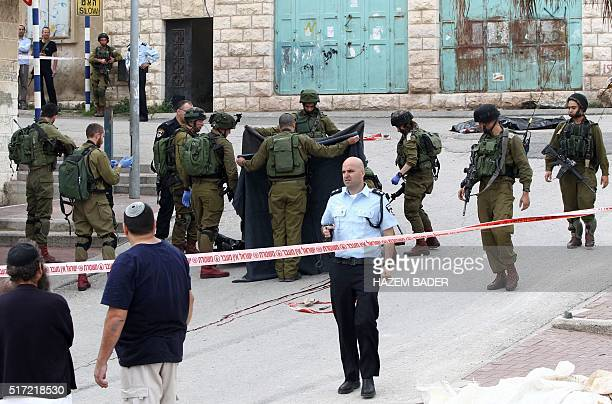 Israeli soldiers cover the body of a Palestinian assailant who was allegedly shot in the head by an Israeli soldier as he lay wounded on the ground...