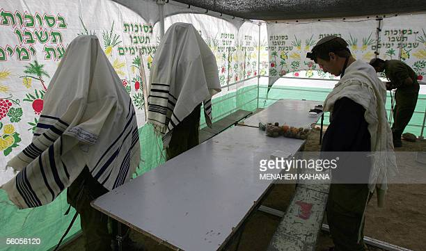 Israeli soldiers covered with Talit perform the morning prayer inside a tent at their position while on alert near Kibbutz Nahal Oz just outside the...