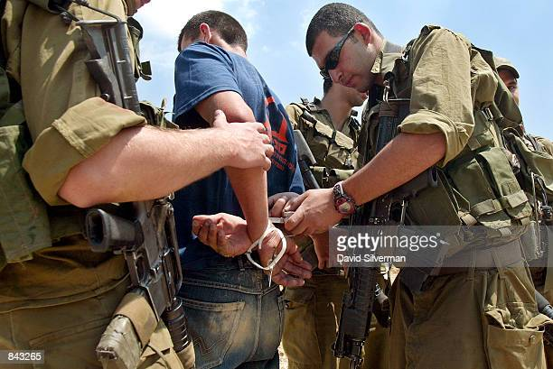Israeli soldiers cuts the ties that bind the wrists of a young Palestinian man after he and another man were caught trying to bypass a military...