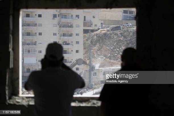 Israeli soldiers demolish a 2 storey building with bulldozers as they have started to demolish buildings belonging to Palestinians on the grounds...