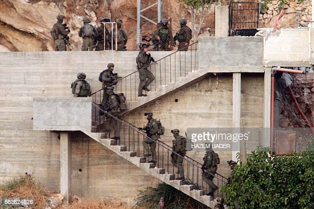 Israeli soldiers deploy near a Palestinian house during a raid to find Mohamed Fakih a Hamas militant accused of murdering an Israeli rabbi earlier...