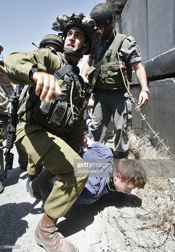 Israeli soldiers detain a European peace activist during a protest against Israel's decision not to allow international aid boat Rachel Corrie to reach the blockaded Gaza Strip, on June 5, 2010 in the West Bank village of Beit Omar.