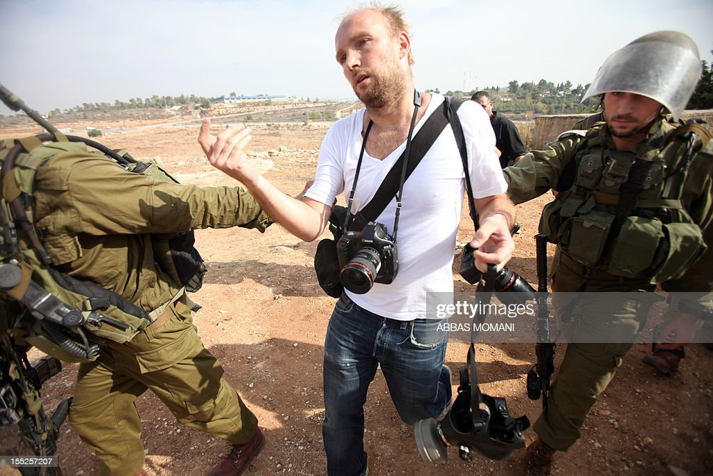Israeli soldiers detain a foreign photographer during a protest against the confiscation of Palestinian land by Israel in the West Bank village of Nabi Saleh near Ramallah on November 2, 2012.